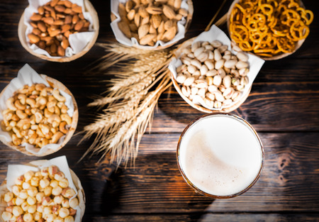 Top view of glass with freshly poured beer near plates with pistachios, small pretzels and peanuts on dark wooden desk. Food and beverages concept