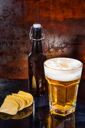 Glass with freshly poured light beer, beer bottle near scattered chips on a black mirror surface. Food and beverages concept Stock Photo