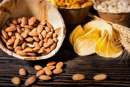 Close up of wooden plate with almonds near wooden plates with snacks on dark wooden desk. Food and beverages concept Stock Photo