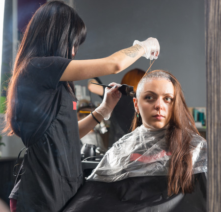 Reflection in large mirror of brunette hairdresser thoroughly dyeing hair of female client while she is sitting in chair in beauty salon
