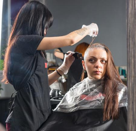 Reflet dans un grand miroir de coiffeur brune en train de teindre les cheveux d'une cliente alors qu'elle est assise sur une chaise dans un salon de beauté