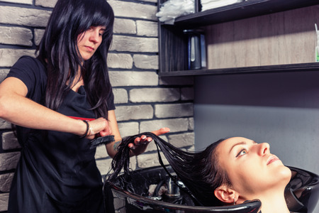 Brunette attractive hairdresser combing hair of young beautiful woman in washing sink in beauty salon 스톡 콘텐츠