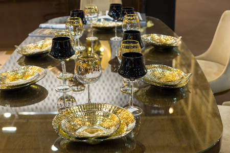 Table setting of glamorous glasses and plates in gold and black color