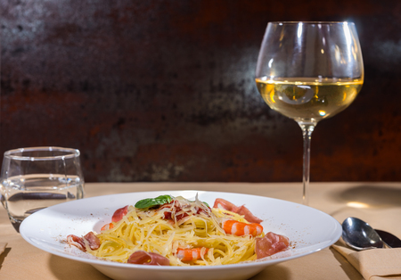 Glass with wine near tasty spaghetti pasta with shrimps, grated cheese, jamon, tomato sauce and basil in white plate on decorated table with light tablecloth