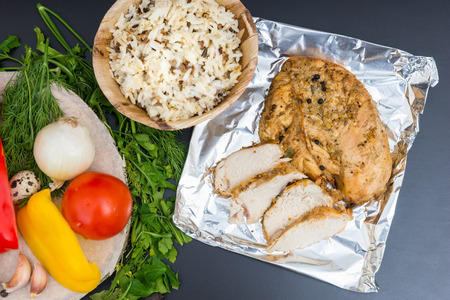 High angle view of baked chicken breast on foil near vegetables and a plate of rice on a gray background