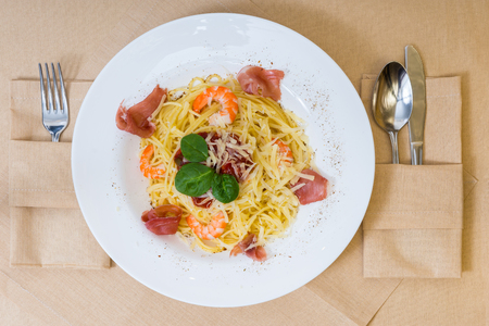 High angle view of spaghetti pasta with shrimps, grated cheese, jamon, tomato sauce and basil in white plate on decorated table with light tablecloth
