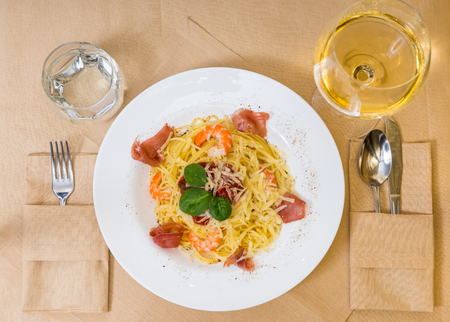High angle view of spaghetti pasta with shrimps, grated cheese, jamon, tomato sauce and basil in white plate near glass with wine and a glass for water on decorated table with light tablecloth