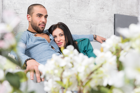 Attractive international couple of man with beard and his brunette wife sitting in an embrace on the sofa in the living room with a fireplace