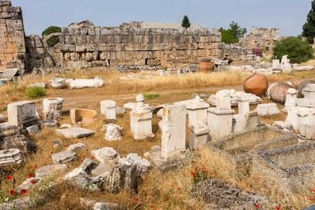 Archeological artefacts from old Greek ruins neatly laid out together on display in the open in front of an ancient stone wall