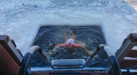Person, die aus einem Schwimmloch hervorgeht, das in die gefrorene Eisoberfläche eines Sees geschnitten ist, gesehen von der Spitze der Ausgangsstufen