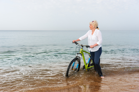 Blond woman wading through the sea pushing a bicycle through the surf as she looks out over the calm ocean Stock Photo