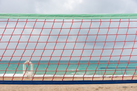 Volley ball net on a deserted tropical beach in a close up detailed view with a lifeguard hut and calm blue ocean in the background on a cloudy day Stock Photo