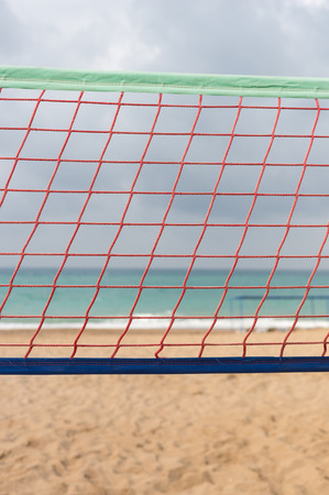 Close up detail of an orange volley ball net at the seaside over a sandy tropical beach with ocean backdrop and cloudy sky