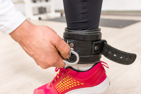 Close Up of Hand Clipping Fastener to Ankle Strap of Young Woman Wearing Bright Colored Running Shoe in Gym