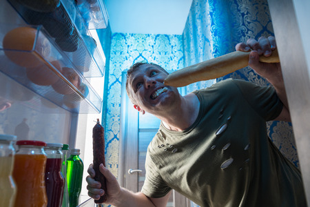 Greedy man munching a baguette and whole salami in the open door of the fridge in his kitchen at night standing with a mouthful of bread