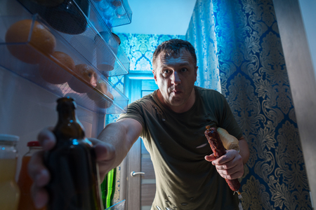 Man grabbing a bottle of cold beer in a fridge as he stands in the open door of the refrigerator holding a whole salami viewed from inside Stock Photo