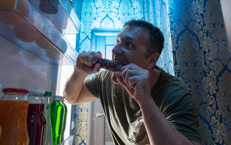 Hungry man snacking on salami from his fridge biting into the whole sausage viewed looking out from inside the open door Stock Photo