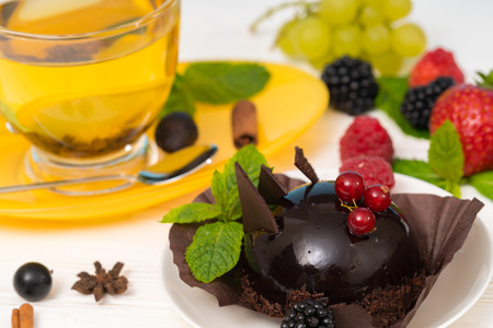 Gourmet dark chocolate bonbon with red currants served with a cup of hot spiced lemon tea and assorted fresh berries with mint Stok Fotoğraf