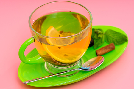 Close-up studio shot of an organic mint tea with lemon and cinammon served in a transparent cup on green saucer against pink background for copy space