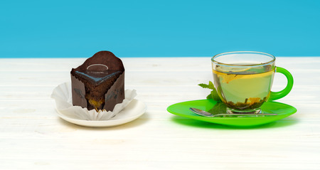 Studio shot close-up of delicious chocolate cake served with organic mint lemon tea on a white table against blue background for copy space