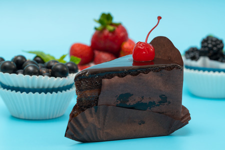 Slice of chocolate cake with fresh berry tartlets Stock Photo