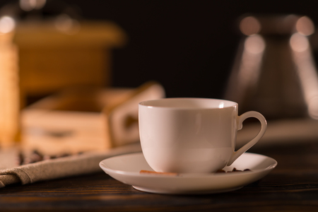 Plain white coffee cup on a wooden kitchen table in a close up low angle side view with a blurred coffee mill behind