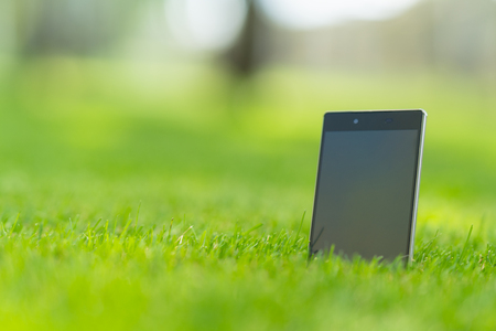 Blank tablet pc with a black screen with copy space standing upright in green grass in a low angle view Stock Photo