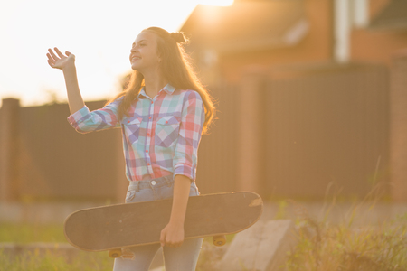 Smiling female teenager wearing jeans and holding skateboard while being illuminated by sunlight causing orange lens flare 免版税图像