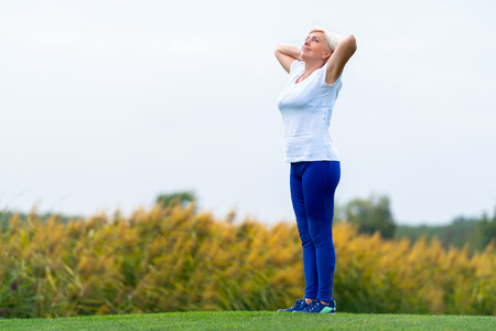 Calm adult woman wearing white tee shirt and dark blue pants with arms behind head standing on large green lawn Stock Photo