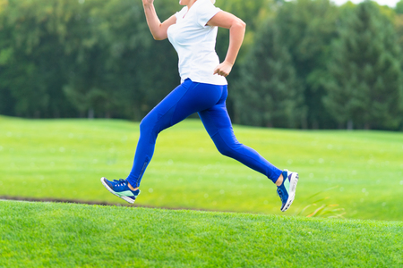 Unidentified adult woman wearing white shirt and blue pants running across large open grassy field with Stock fotó