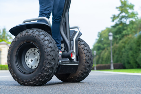 Woman riding a Segway personal transporter in a low angle view of the wheels and her legs on an asphalt road