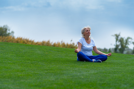 Senior woman relaxing on green grass during meditation