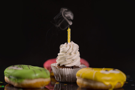 Extinguished candle on a birthday cupcake decorated with twirled icing emitting a plume of smoke in a side angle view Stock Photo