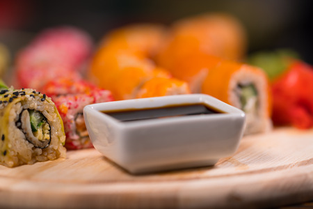 Bowl of soy sauce on a sushi board with fresh raw fish and seaweed rolls in a close up low angle view Фото со стока