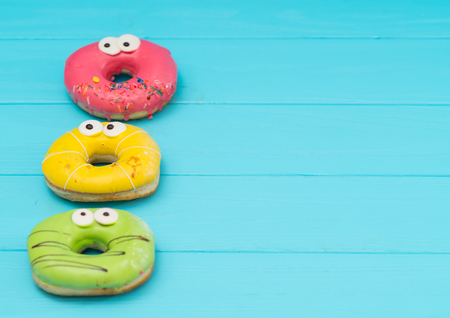 Three fun iced donuts with googly eyes and colorful yellow, green, and pink icing on a blue wood background with copy space