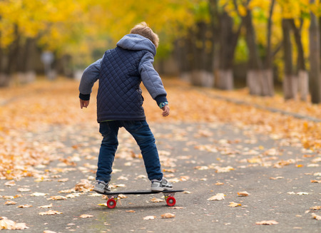 Young boy in grey jacket standing on the skateboard viewed full-length from his back in park walkway covered with yellow leaves