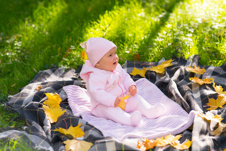 Little baby girl in a sunny autumn park sitting on a blanket on the grass surrounded by scattered yellow leaves