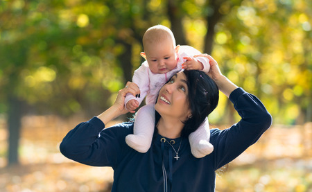 Young mother with her baby daughter on her shoulders smiling as she looks up while playing in a sunny colorful autumn park