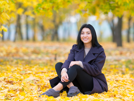 Attractive trendy young woman sitting amongst autumn leaves in a park smiling happily at the camera