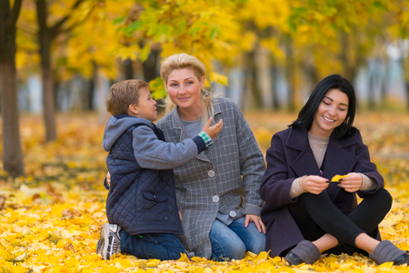A happy same sex female couple and their son in an autumn park setting.