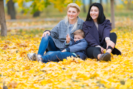 A happy same sex female couple and their son in a happy family theme with yellow fall leaves. 스톡 콘텐츠