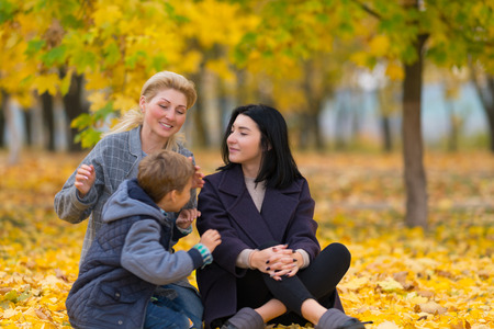 A same sex female couple with their son in a happy family portrait at a city park with yellow fall leaves. 免版税图像