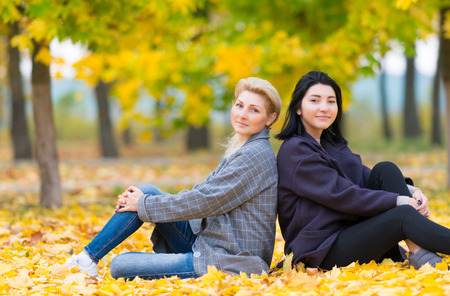 Attractive mother and daughter relaxing in a park sitting together back to back on colorful yellow autumn leaves 版權商用圖片