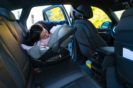 Mother kissing her baby in baby seat on the backseat of the car with black interior, viewed from other side of the vehicle with copy space Stock Photo