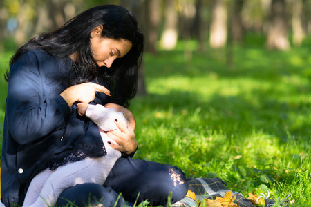 A loving mother discreetly breastfeeding her baby in lush city park. Stok Fotoğraf