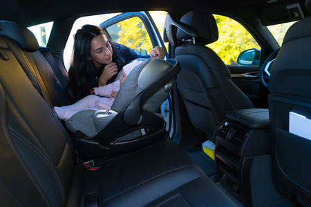 Young mother checking her baby in car safety seat, sitting on the backseat of the car with black interior, viewed from the side with copy space