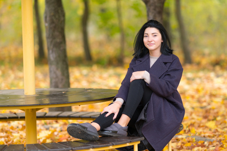 Woman relaxing on a wooden bench in an autumn park smiling at the camera surrounded by colorful leaves