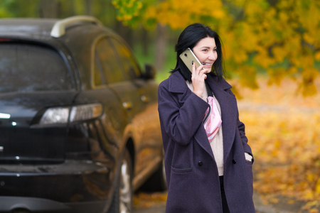 happy young woman talking on her mobile outdoors in an autumn park as she stands waiting alongside her car
