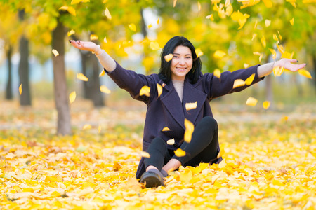 Happy young woman throwing autumn leaves in the air as she sits on the ground in a wooded park smiling at the camera 版權商用圖片