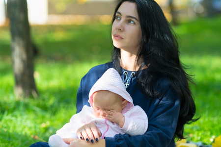 A wistful looking, young mother holding a sleepy baby in lush city parkland.